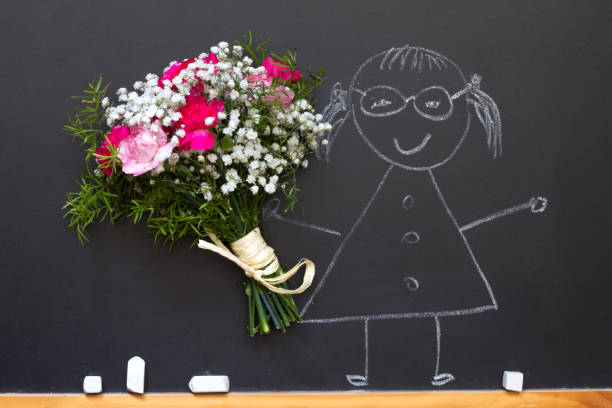 girl with bouquet of flowers on blackboard teacher day abstract concept - teachers day stock photos and pictures