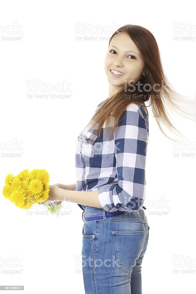 Girl with bouquet yellow wildflowers. Teenage in jeans. stock photo
