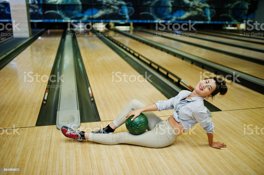 Girl with bowling ball on alley played at bowling club. stock photo