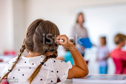 istock Girl with braided hair sitting at desk in class 1071268078
