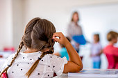 Girl with braided hair sitting at desk in class