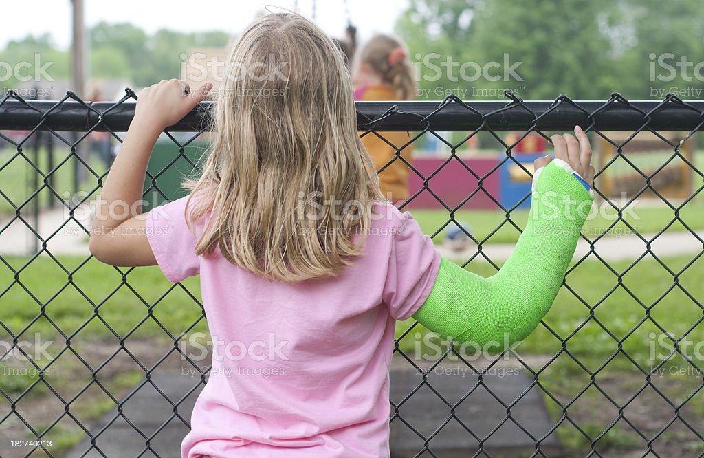 Chica con brazo fracturado desea podría desempeñar en el patio de juegos. - foto de stock