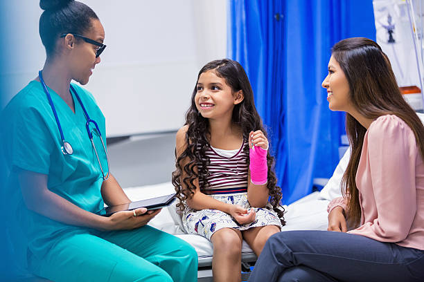 Girl with broken wrist being treated in hospital emergency room stock photo