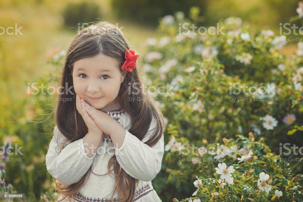Fille avec cheveux brune et les yeux bruns élégants habillé village rustique portant vêtements blanc rouge et chemise pantalon ceinture posant avec des fleurs dans les prés de la forêt - Photo
