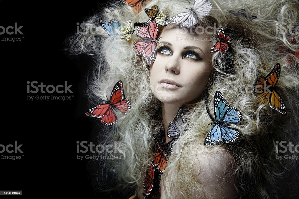 Girl with butterfly in curly blond hair. royalty-free stock photo