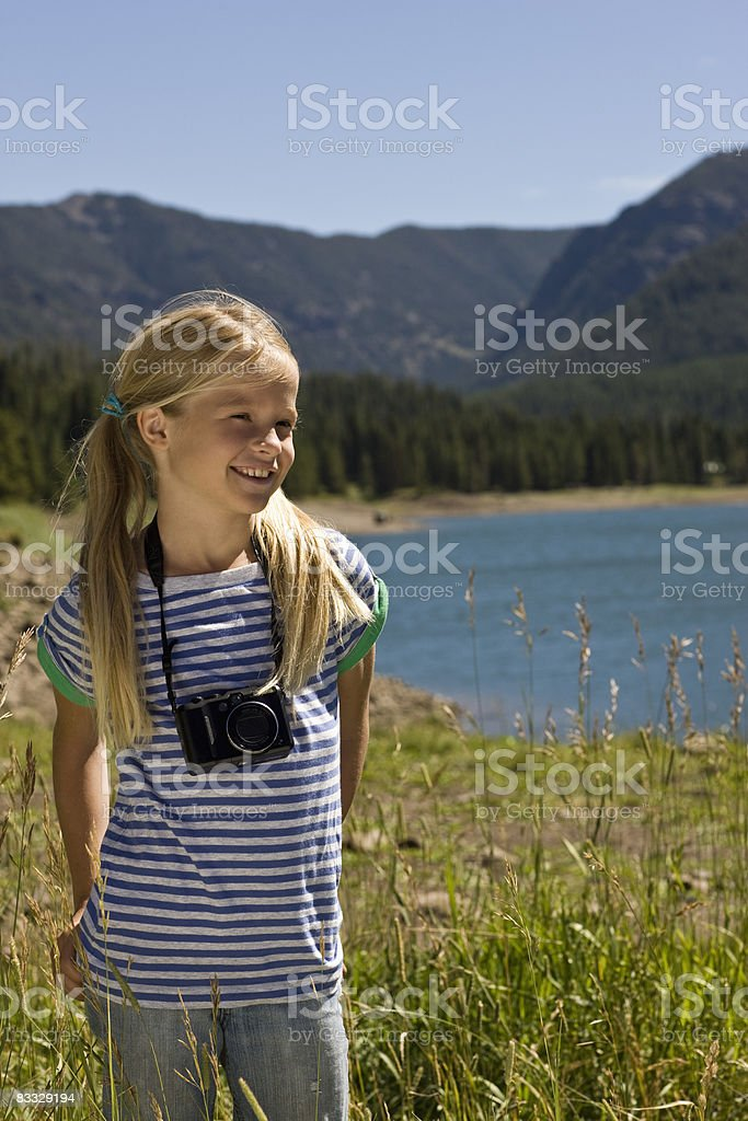 Girl with camera around neck by lake royalty free stockfoto