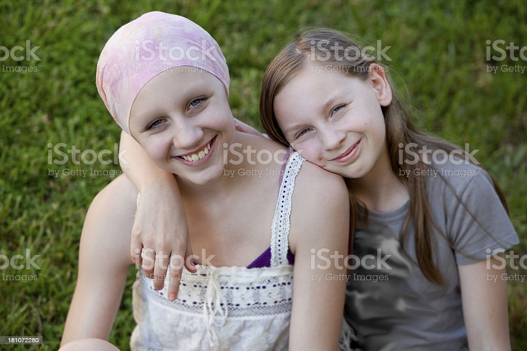 Girl with Cancer and Loving Sister stock photo