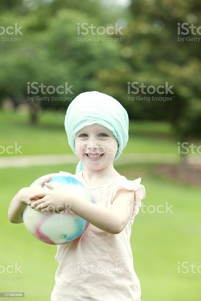 Girl with Cancer Playing in the Park stock photo