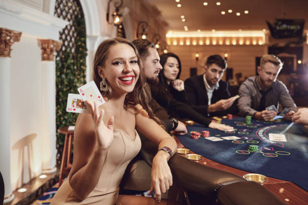 Girl with cards in her hands smiling plays poker in a casino. stock photo