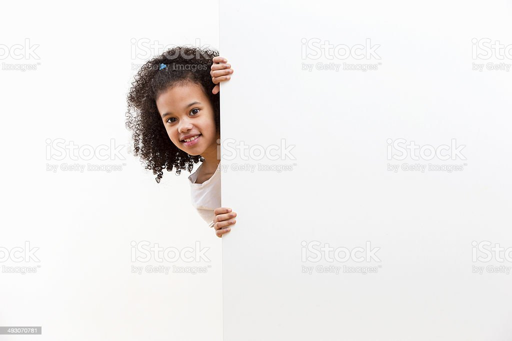 Girl With Cheeky Face Looking Around White Wall In Studio stock photo
