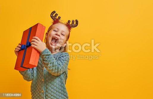 Happy little girl with Christmas gift on bright color background. Yellow, red and teal.