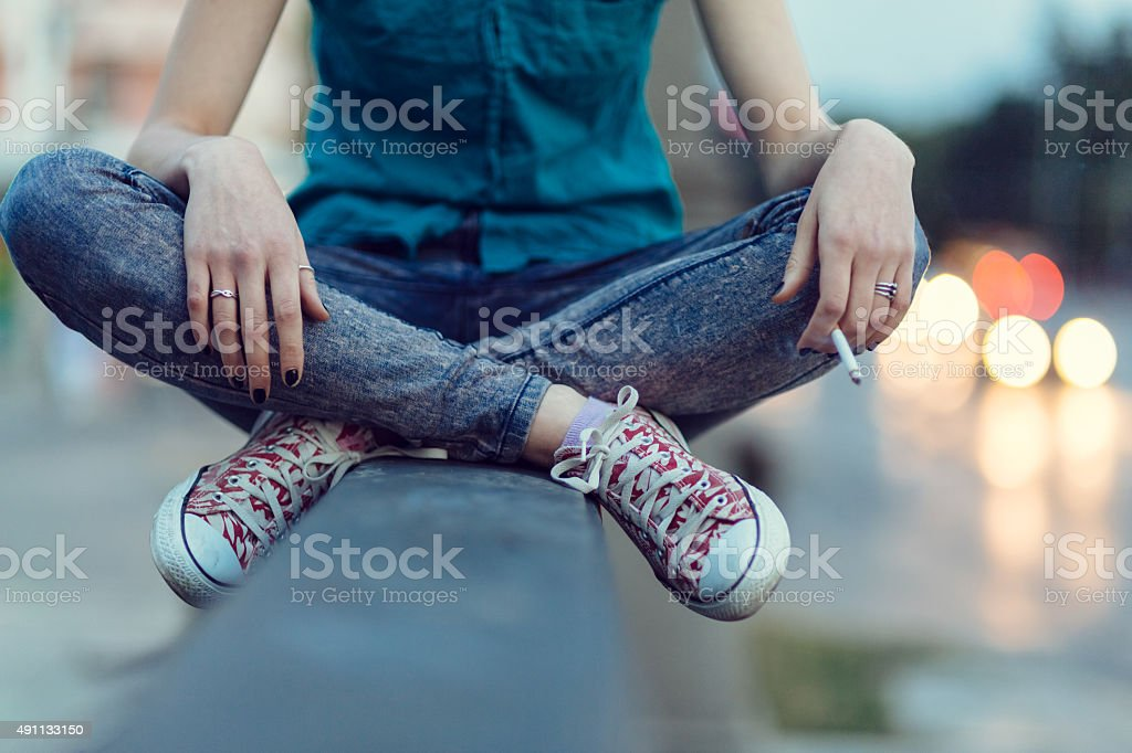 Girl with cigarette outside stock photo