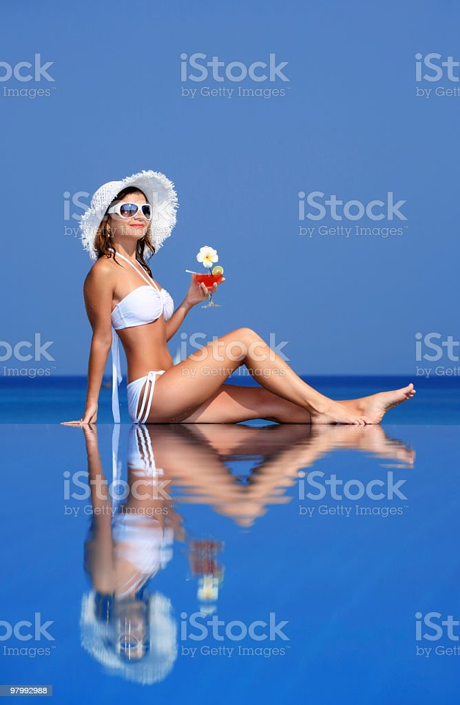 Girl with cocktail sitting on the water. royalty-free stock photo