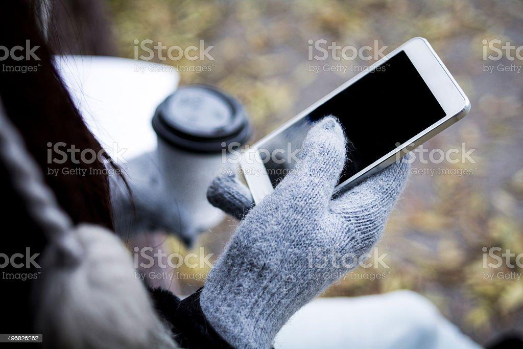 Mädchen mit Kaffee und Handy - Lizenzfrei Handschuh Stock-Foto