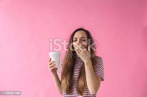istock Girl with coffee is yawning. 1138361485