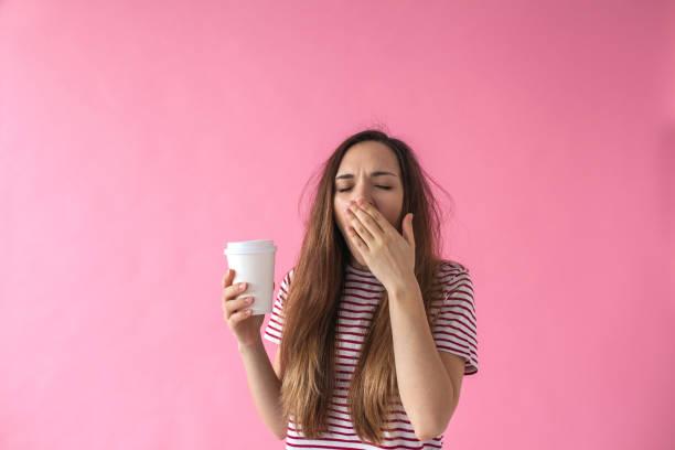 girl with coffee is yawning. - stanco foto e immagini stock