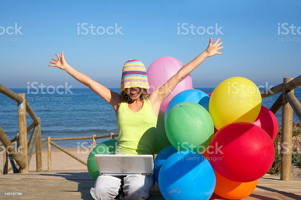 girl with colored balloons using a laptop on the beach royalty-free stock photo