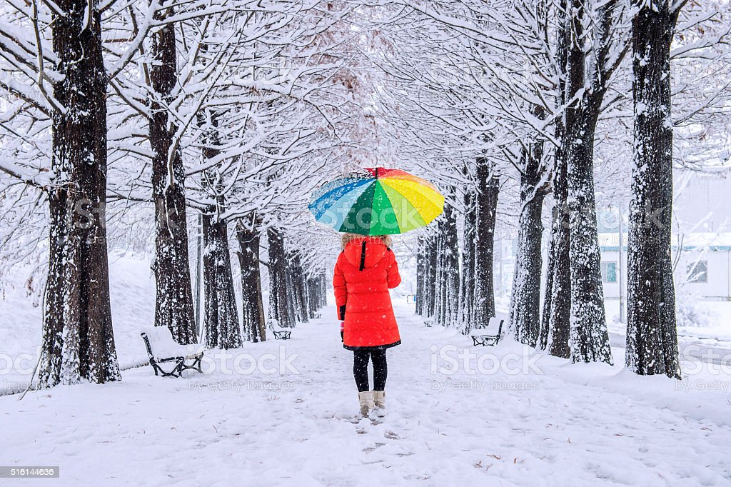 Girl with colourful umbrella walking on the path stock photo