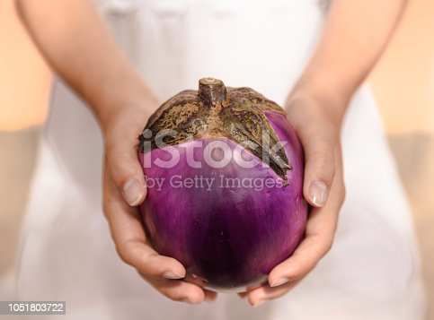 Girl dressed in white holds, holding a big purple, pink courgette, vegetable