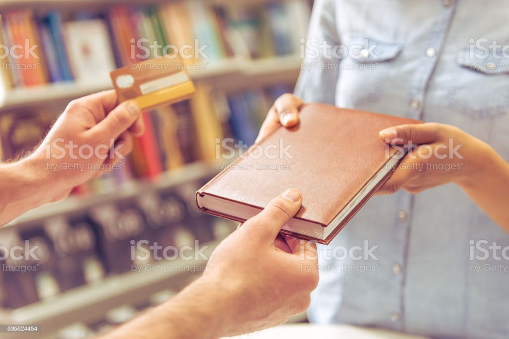 Girl with credit card at the bookshop stock photo