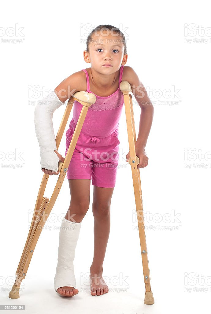 Girl with crutches stock photo
