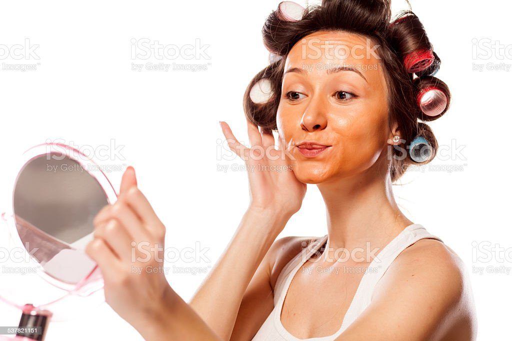 Girl with curlers and wrong liquid foundation on her face stock photo