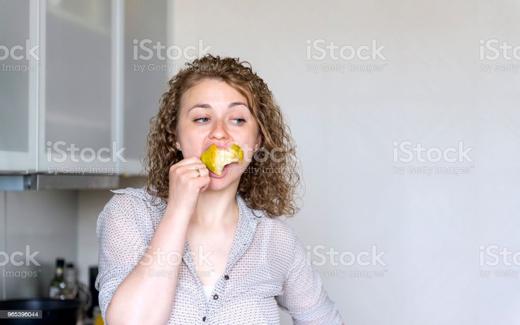 girl with curly hair eating pear, young woman eating fruit zbiór zdjęć royalty-free
