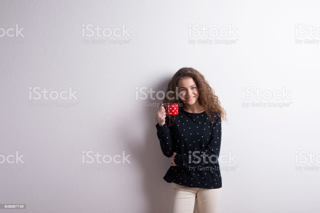 Teenage girl with long curly hair wearing blue sweatshirt holding red...