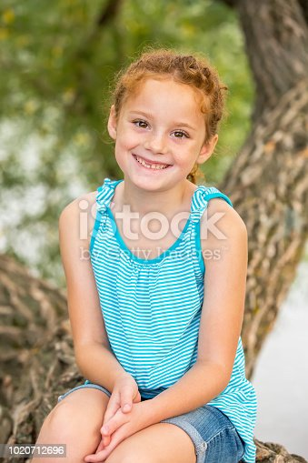 Close-up front view of a girl with curly red hair sitting on a large tree limb overhanging the Mississippi River. The girl is wearing a blue and white striped tank top and denim jean shorts. She is smiling and looking at the camera.