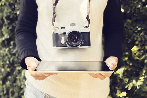 Girl with digital tablet and old photo camera outdoors stock photo