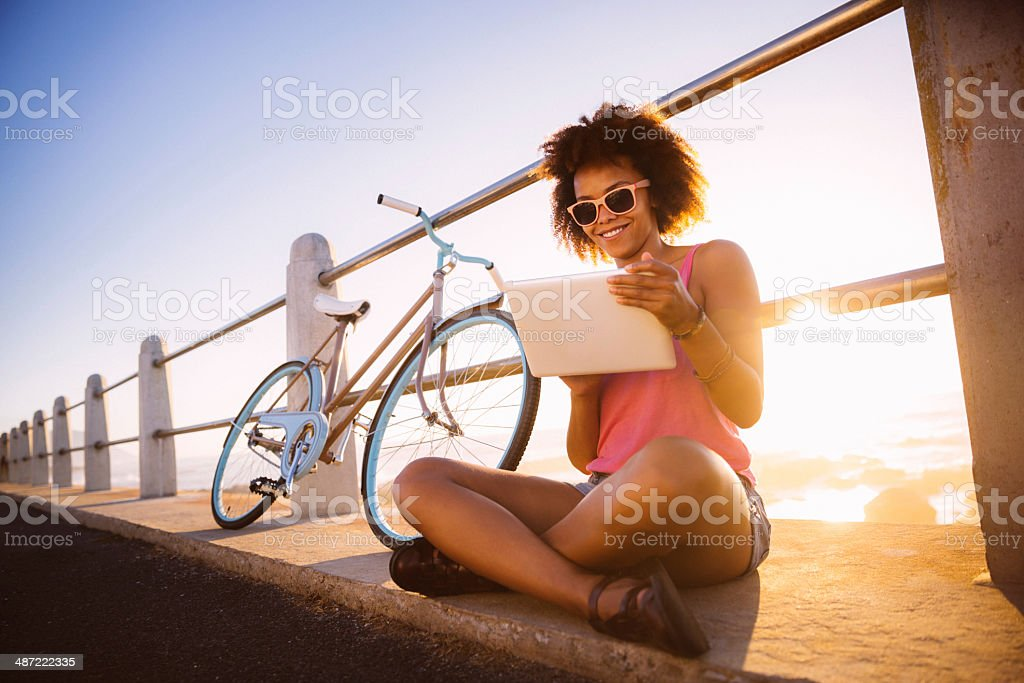 Girl with digital tablet near beach stock photo