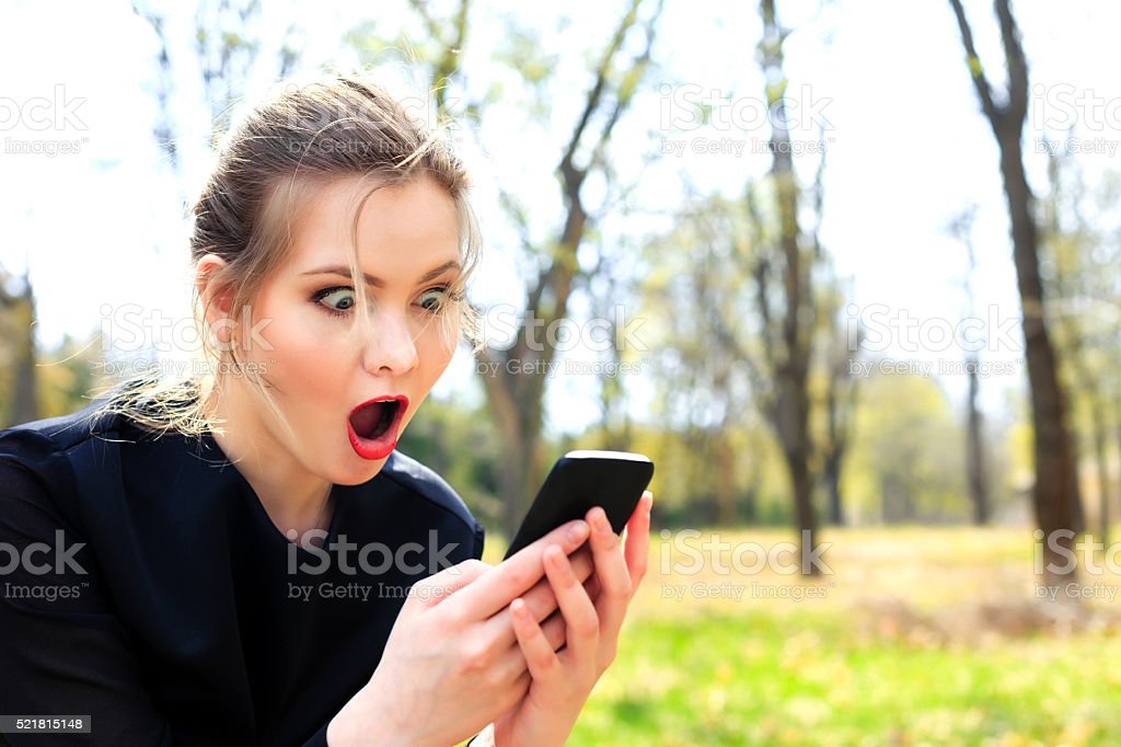 Girl with disheveled hair and open mouth stares into smartphone stock photo