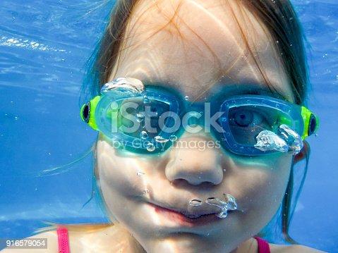 Ein Mädchen mit Tauchbrille taucht im Pool und hält die Luft an, Porträt