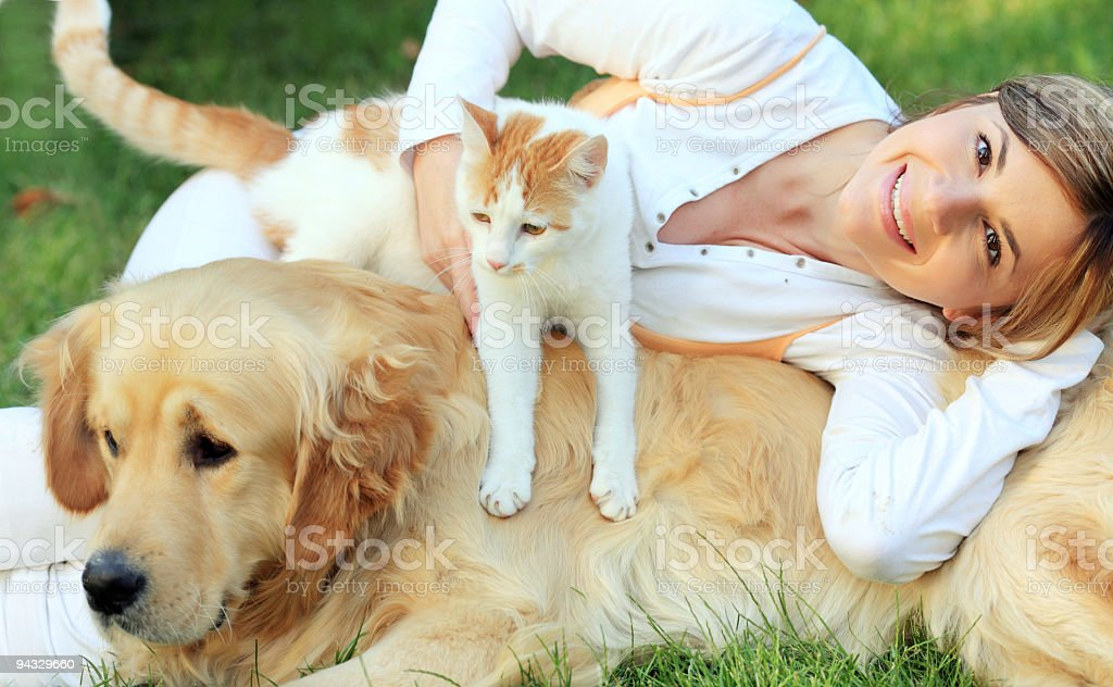 Girl with dog and cat resting on the green grass. royalty-free stock photo