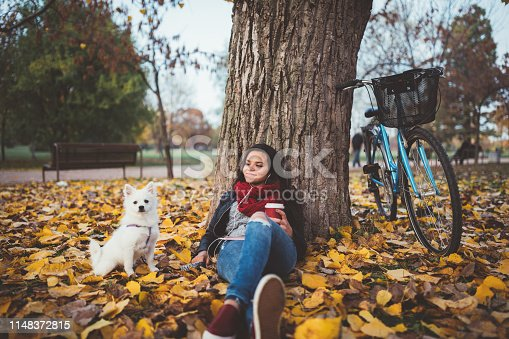 Relaxed girl with her dog drinking coffee in the park