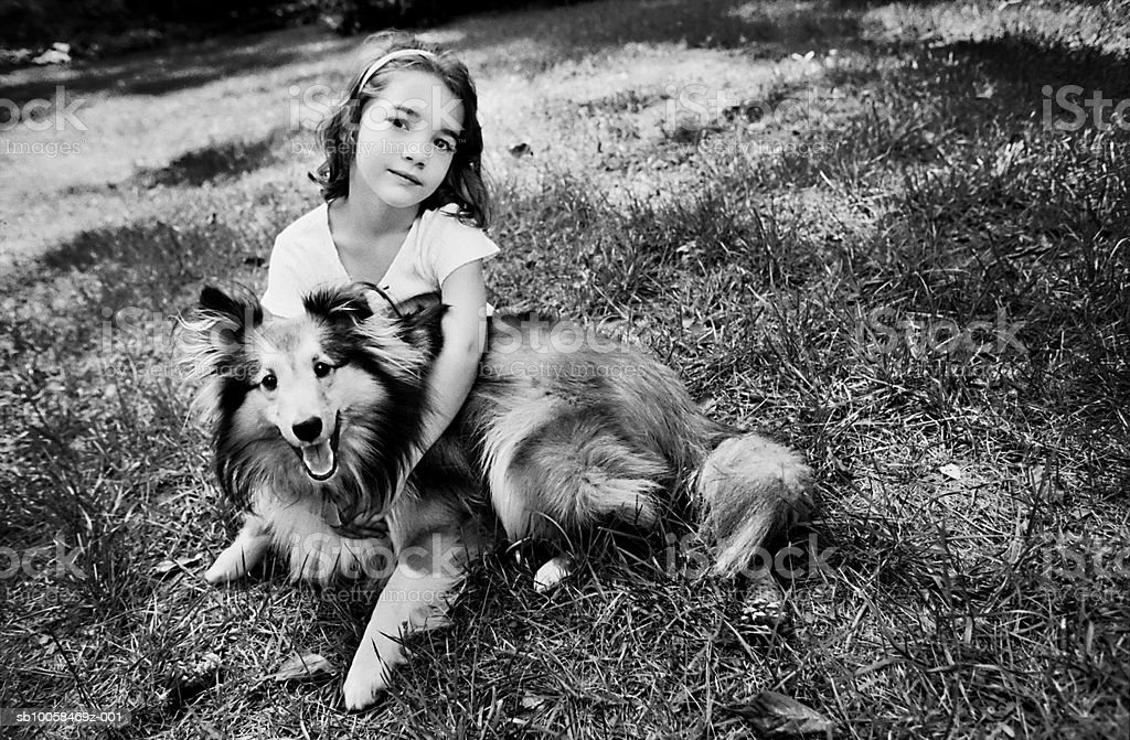 Girl (5-7) with dog on lawn, portrait (B&W) royalty-free stock photo