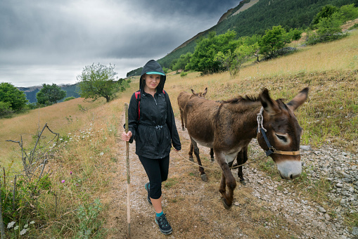 Girl with donkey in Italian mountains