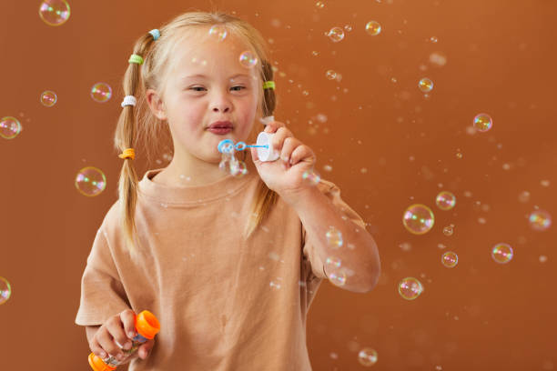 Girl with Down Syndrome Blowing Bubbles stock photo