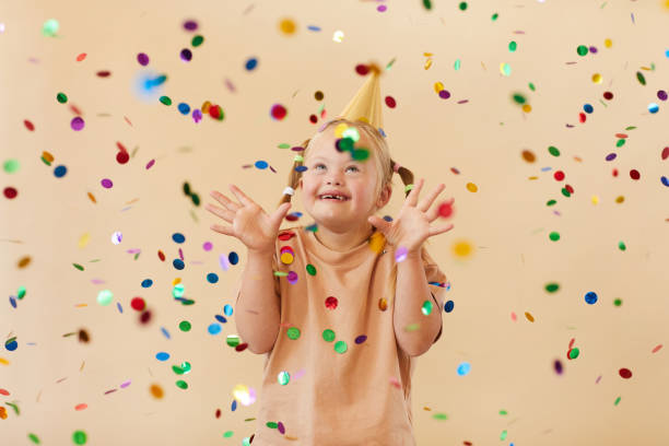 Girl with Down Syndrome Celebrating Birthday at Party stock photo