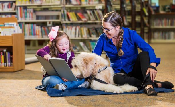Mädchen mit Down-Syndrom in Bibliothek mit Therapiehund – Foto