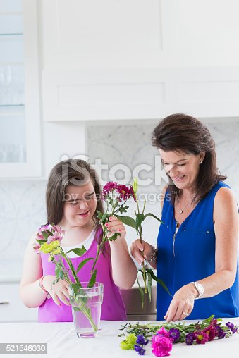 623358818 istock photo Girl with down syndrome, mother arranging flowers 521546030