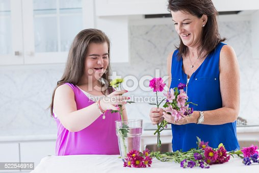 623358818 istock photo Girl with down syndrome, mother arranging flowers 522546916