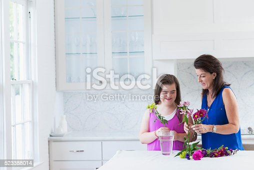 623358818 istock photo Girl with down syndrome, mother arranging flowers 523388014
