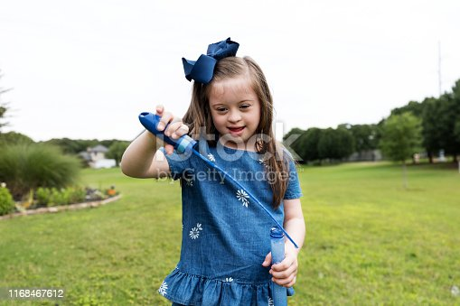 While playing outside, the young girl with Down Syndrome poses for the camera.