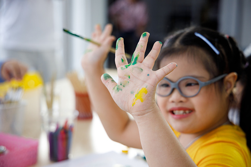 Happy Asian girl with Down's syndrome painting her hand with water color in art class.