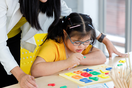 Asian girl with Down's syndrome play puzzle toy with her teacher in classroom.