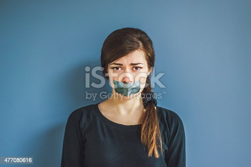 istock girl with duct tape over her mouth 477080616