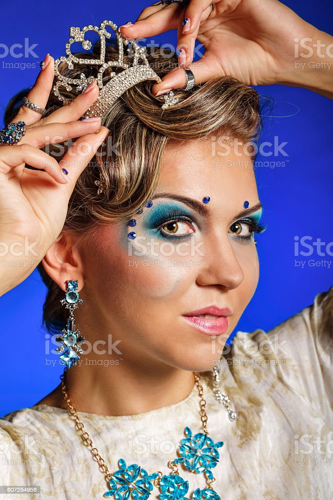 Girl with face art, jewelry, hair and tiara. stock photo