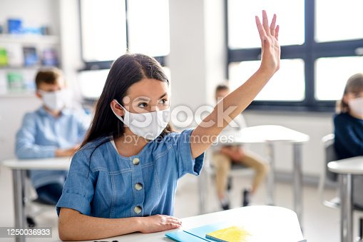 Girl with face mask back at school after covid-19 quarantine and lockdown, raising hand.
