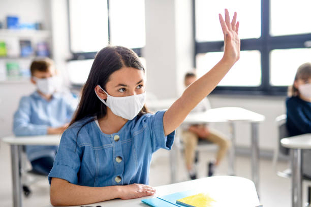 Girl with face mask back at school after covid-19 quarantine and lockdown. stock photo
